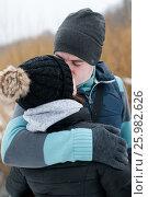 Купить «Счастливая пара. Молодые мужчина и женщина целуются зимой на улице», эксклюзивное фото № 25982626, снято 24 февраля 2017 г. (c) Игорь Низов / Фотобанк Лори