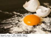 Разбитое яйцо с мукой на черном столе. Стоковое фото, фотограф Галина Жигалова / Фотобанк Лори