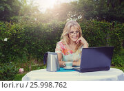 Pretty blonde woman with computer drink coffe and talk to mobile in the garden. Стоковое фото, фотограф Александр Новиков / Фотобанк Лори