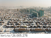 Купить «Top view of Urban contrasts in Astana, Kazakhstan. Small private houses on the background of new high houses.», фото № 26005278, снято 23 февраля 2019 г. (c) Андрей Орехов / Фотобанк Лори