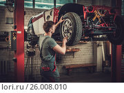 Купить «Mechanic working on classic car wheels and suspension in restoration workshop», фото № 26008010, снято 6 апреля 2017 г. (c) Andrejs Pidjass / Фотобанк Лори