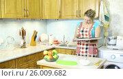 Купить «Молодая домохозяйка читает кулинарную книгу, стоя на кухне перед столом со спелыми яблоками», видеоролик № 26009682, снято 5 марта 2017 г. (c) Сергей Дубров / Фотобанк Лори