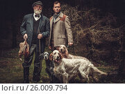 Купить «Two hunters with dogs and shotguns in a traditional shooting clothing.», фото № 26009794, снято 18 октября 2018 г. (c) Andrejs Pidjass / Фотобанк Лори