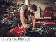 Купить «Mechanic working on classic car electrics in restoration workshop», фото № 26009850, снято 6 апреля 2017 г. (c) Andrejs Pidjass / Фотобанк Лори