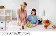 Купить «happy family cooking salad at home kitchen», видеоролик № 26017078, снято 5 апреля 2017 г. (c) Syda Productions / Фотобанк Лори
