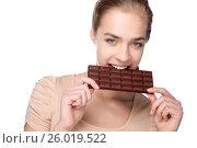 Купить «Girl holding big chocolate bar in her tooth», фото № 26019522, снято 24 марта 2012 г. (c) Tatjana Romanova / Фотобанк Лори