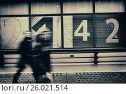 Dos personas andando en movimiento irreconociles, al fondo una fachada con numeros 2-1-4-2. London, UK, Europa. Стоковое фото, фотограф Lluís Real / age Fotostock / Фотобанк Лори