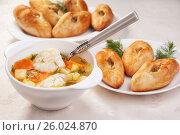 Вкусные домашние традиционные русские рыбный суп-уха и пирожки с рыбной начинкой-расстегаи в тарелках на столе. Стоковое фото, фотограф Анастасия Богатова / Фотобанк Лори