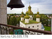 Купить «Upper view of ancient Church of St John the Baptist with green domes and a cityscape behind it in Kargopol, Arkhangelsk region, Russia. A bell in the foreground», фото № 26035178, снято 12 августа 2015 г. (c) Алексей Мараховец / Фотобанк Лори