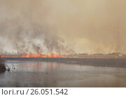 Купить «Масштабный поджог камыша на реке. Видны вдали сельские дома в дыму. Пожар.», фото № 26051542, снято 22 апреля 2017 г. (c) Нина Карымова / Фотобанк Лори