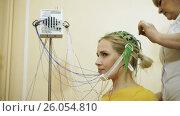 Купить «Electroencephalographic examination. The female doctor preparing young blond-haired woman for brain scan in the hospital. HD», видеоролик № 26054810, снято 3 апреля 2017 г. (c) ActionStore / Фотобанк Лори
