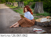 Девушка читает книгу в аллее срубленных деревьев. Стоковое фото, фотограф София Тюленева / Фотобанк Лори