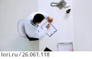 Купить «doctor with cardiogram on clipboard at clinic», видеоролик № 26061118, снято 23 января 2020 г. (c) Syda Productions / Фотобанк Лори