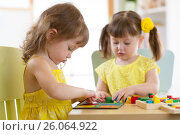 Купить «Kids playing with logical toy on desk in nursery room or kindergarten. Children arranging and sorting shapes, colors and sizes.», фото № 26064922, снято 5 апреля 2017 г. (c) Оксана Кузьмина / Фотобанк Лори