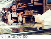 Купить «Male shop assistant demonstrating delicious loaves of bread in bakery», фото № 26077550, снято 26 января 2017 г. (c) Яков Филимонов / Фотобанк Лори