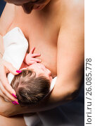 Купить «Mother breast feeding her child», фото № 26085778, снято 27 мая 2019 г. (c) Игорь Бородин / Фотобанк Лори
