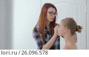 Makeup artist applying liquid tonal foundation on girl's face. Стоковое видео, видеограф Aleksey Popov / Фотобанк Лори
