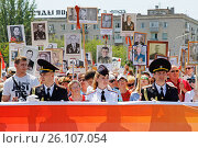 Volgograd, Russia - May 09, 2016: People hold banner of Immortal regiment and portraits of their relatives on Victory day in Volgograd. Редакционное фото, фотограф Юлия Олейник / Фотобанк Лори