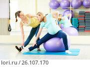 Купить «pregnant woman doing fitness ball exercise with coach», фото № 26107170, снято 3 марта 2017 г. (c) Дмитрий Калиновский / Фотобанк Лори