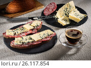 Sandwiches with cheese of Dorblu and raw smoked sausage on black slate plates, a cheese knife and a cup of hot coffee, фото № 26117854, снято 29 апреля 2017 г. (c) Anatoly Timofeev / Фотобанк Лори