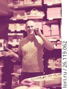 Купить «Adult man in front of difficult choice in store», фото № 26119062, снято 29 августа 2016 г. (c) Яков Филимонов / Фотобанк Лори