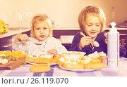 Купить «Two little girls enjoying pastry with cream», фото № 26119070, снято 14 декабря 2018 г. (c) Яков Филимонов / Фотобанк Лори