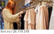 Купить «Red hair woman in a clothing store chose a dress - shopping concept», видеоролик № 26119318, снято 18 января 2020 г. (c) Константин Шишкин / Фотобанк Лори