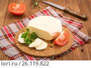 Нарезанный адыгейский сыр, помидор и листья петрушки на подложке на деревянном столе. Стоковое фото, фотограф Елена Руй / Фотобанк Лори