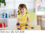 Купить «Kid girl playing with logical toy on desk in nursery room or kindergarten. Child arranging and sorting colors and sizes», фото № 26121634, снято 20 апреля 2017 г. (c) Оксана Кузьмина / Фотобанк Лори