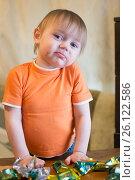 Купить «Маленький мальчик ест конфеты за столом», эксклюзивное фото № 26122586, снято 28 апреля 2017 г. (c) Землянникова Вероника / Фотобанк Лори