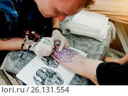 Купить «Tattoo master make tattoo for rocker man at tattoo salon», фото № 26131554, снято 21 августа 2018 г. (c) easy Fotostock / Фотобанк Лори