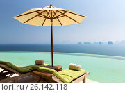 Купить «infinity pool with parasol and sun beds at ocean», фото № 26142118, снято 15 февраля 2015 г. (c) Syda Productions / Фотобанк Лори