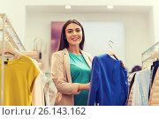 Купить «happy young woman choosing clothes in mall», фото № 26143162, снято 19 февраля 2016 г. (c) Syda Productions / Фотобанк Лори