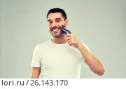 Купить «smiling man shaving beard with trimmer over gray», фото № 26143170, снято 15 января 2016 г. (c) Syda Productions / Фотобанк Лори