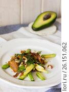 Fresh avocado salad with bacon, nuts and greens on white plate. Стоковое фото, фотограф Галина Жигалова / Фотобанк Лори