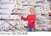Купить «Female shop assistant demonstrating assortment at textile shop», фото № 26156434, снято 15 февраля 2017 г. (c) Яков Филимонов / Фотобанк Лори
