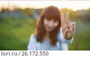Купить «Woman Showing a Peace Sign at Sunset», видеоролик № 26172550, снято 4 мая 2017 г. (c) Илья Шаматура / Фотобанк Лори