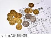 Купить «Металлические деньги лежат на счёте на квартплату», фото № 26186058, снято 15 марта 2017 г. (c) Максим Мицун / Фотобанк Лори