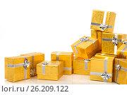 Купить «A pile of gold gifts on white», фото № 26209122, снято 18 августа 2012 г. (c) Tatjana Romanova / Фотобанк Лори