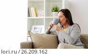 Купить «happy woman drinking tea or coffee at home», видеоролик № 26209162, снято 29 марта 2020 г. (c) Syda Productions / Фотобанк Лори