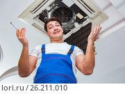 Купить «The worker repairing ceiling air conditioning unit», фото № 26211010, снято 10 марта 2017 г. (c) Elnur / Фотобанк Лори