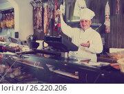Купить «butcher with wurst at counter», фото № 26220206, снято 5 октября 2016 г. (c) Яков Филимонов / Фотобанк Лори