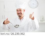 Купить «Positive young cook holding soup ladle», фото № 26230362, снято 20 июня 2019 г. (c) Яков Филимонов / Фотобанк Лори