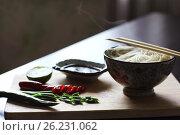 Рисовая лапша с палочками, перец чили, лайм, зеленый лук на деревянной доске. Контровый свет. Стоковое фото, фотограф Галина Жигалова / Фотобанк Лори