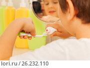 Купить «Little boy spreading toothpaste on a toothbrush», фото № 26232110, снято 19 марта 2017 г. (c) Сергей Новиков / Фотобанк Лори
