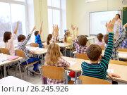 Купить «group of school kids raising hands in classroom», фото № 26245926, снято 15 ноября 2014 г. (c) Syda Productions / Фотобанк Лори