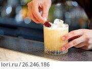 Купить «bartender with glass of cocktail and cherry at bar», фото № 26246186, снято 7 февраля 2017 г. (c) Syda Productions / Фотобанк Лори