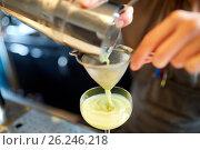 Купить «bartender pouring cocktail into glass at bar», фото № 26246218, снято 7 февраля 2017 г. (c) Syda Productions / Фотобанк Лори