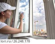 Купить «Девушка моет окно на лоджии. Работница клининговой компании. Строительная площадка за окном на заднем плане», фото № 26248178, снято 2 мая 2017 г. (c) Светлана Ельцова / Фотобанк Лори