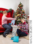 Купить «Young woman at the Christmas tree unpacking presents», фото № 26261118, снято 19 ноября 2017 г. (c) Mikhail Starodubov / Фотобанк Лори